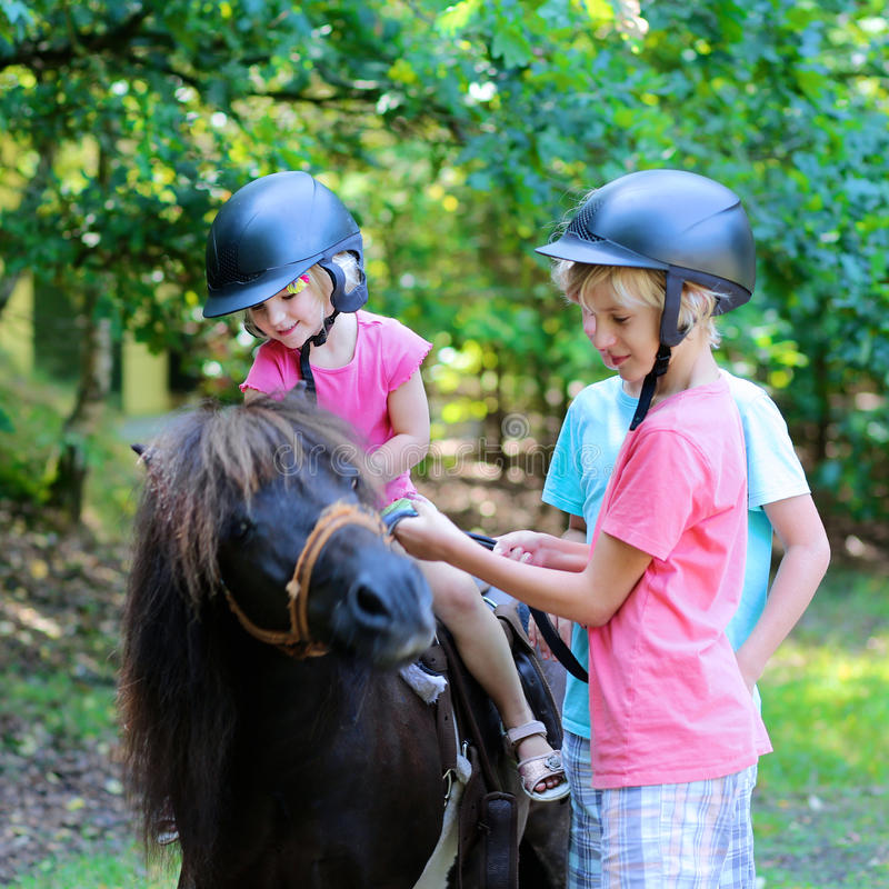 Kids having fun at horse riding summer camp royalty free stock photography