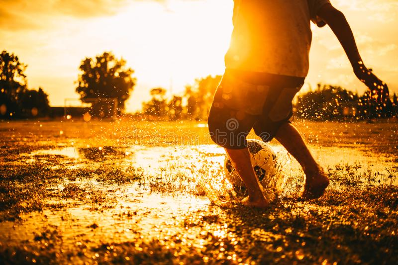 Kids are playing soccer football for exercise under the sunlight. Silhouette and film picture style. royalty free stock photos