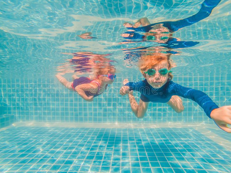 Kids having fun playing underwater in swimming pool on summer vacation royalty free stock photos