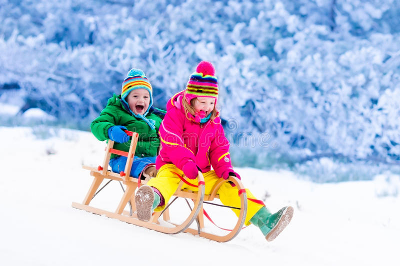 Kids having fun on sleigh ride. Little girl and boy enjoy a sleigh ride. Child sledding. Toddler kid riding a sledge. Children play outdoors in snow. Kids sled stock photos