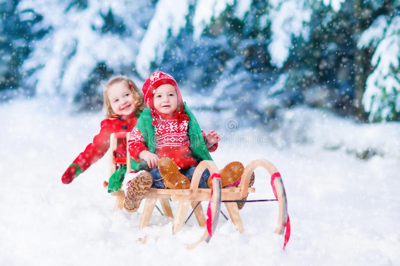 Kids having fun on a sleigh ride in winter. Little girl and boy enjoy a sleigh ride. Child sledding. Toddler kid riding a sledge. Children play outdoors in snow royalty free stock photography