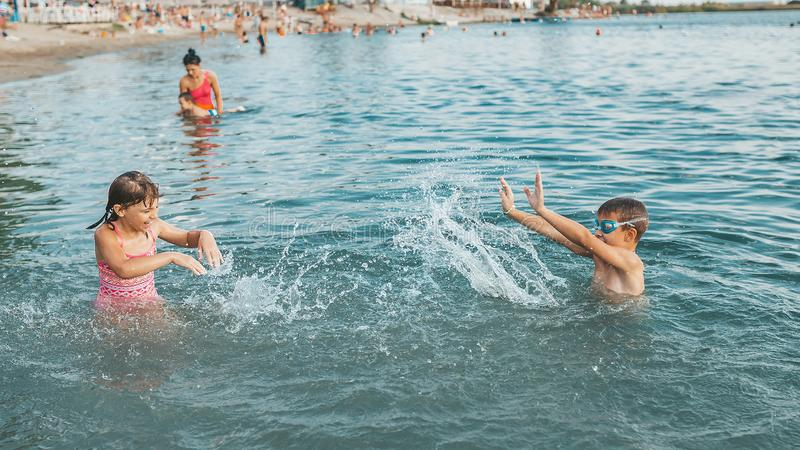 Kids having fun with splashes in the water royalty free stock image