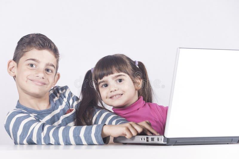 Kids having fun using a laptop computer royalty free stock images