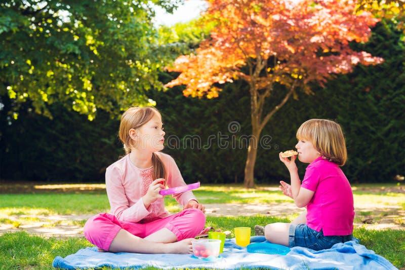 Kids having a picnic outdoors stock photo