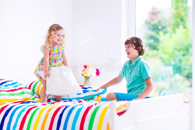 Kids having pillow fight. Two children, happy laughing boy and cute curly little girl having fun at pillow fight with feathers in the air jumping, laughing and stock image