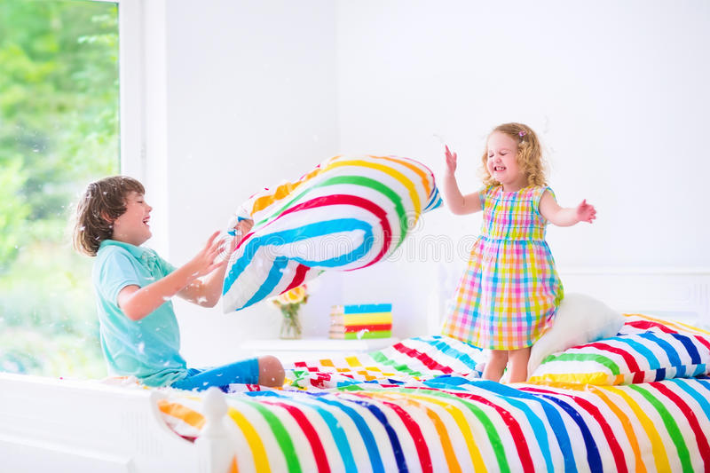 Kids having pillow fight. Two children, happy laughing boy and cute curly little girl having fun at pillow fight with feathers in the air jumping, laughing and stock photo