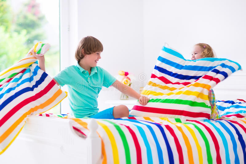 Kids having pillow fight. Two children, happy laughing boy and cute curly little girl having fun at pillow fight with feathers in the air jumping, laughing and royalty free stock image