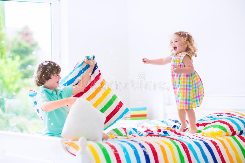 Kids having pillow fight. Two children, happy laughing boy and cute curly little girl having fun at pillow fight with feathers in the air jumping, laughing and stock photography