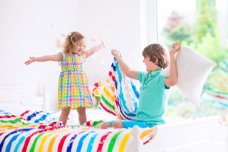 Kids having pillow fight. Two children, happy laughing boy and cute curly little girl having fun at pillow fight with feathers in the air jumping, laughing and royalty free stock photos