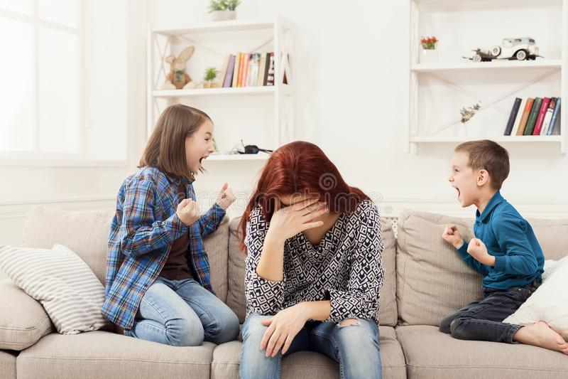 Kids having quarrel over tired mother stock photos