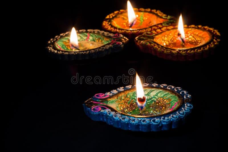 Four burning colorful candles indian style for Diwali celebration. Black background. stock photos