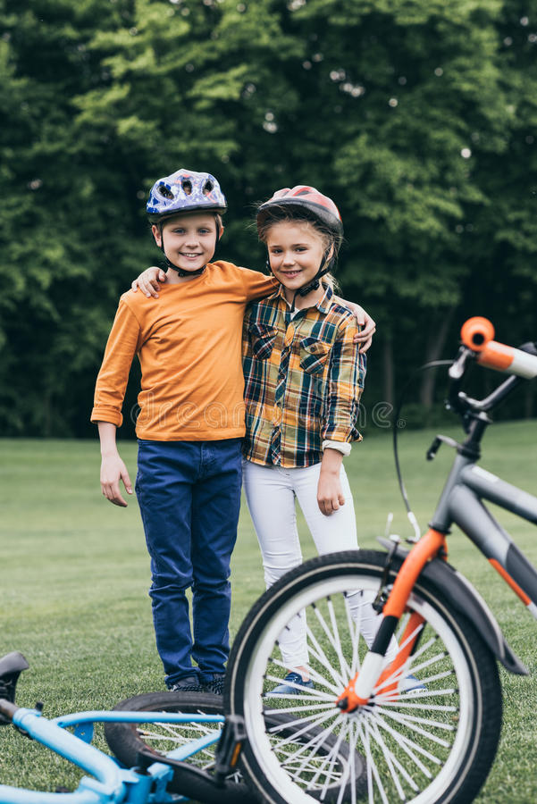 Kids in helmets embracing and looking at camera while standing near bicycles at park stock photography