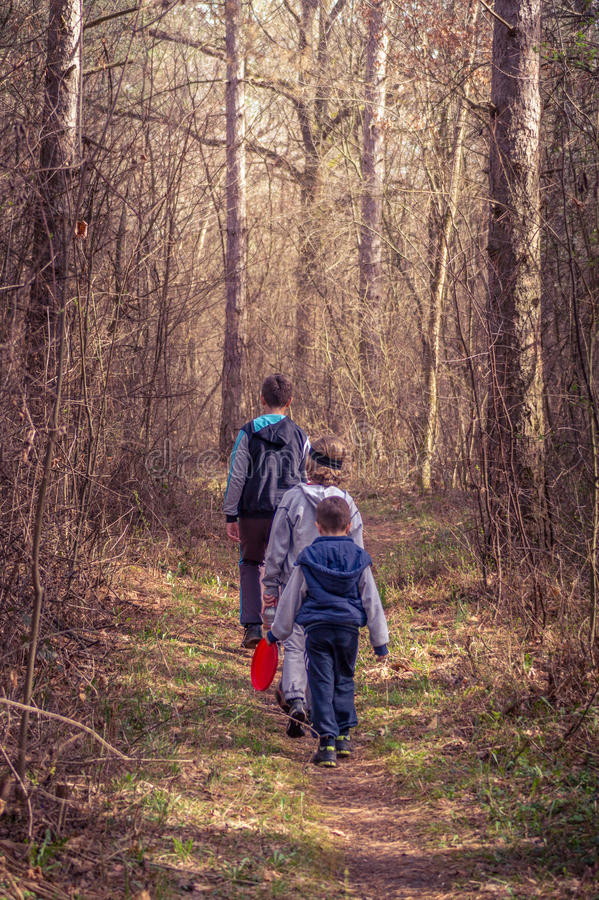 Kids hiking through a forest stock images