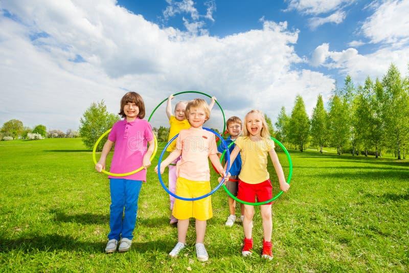 Kids hold hula hoops during exercising activity royalty free stock photo