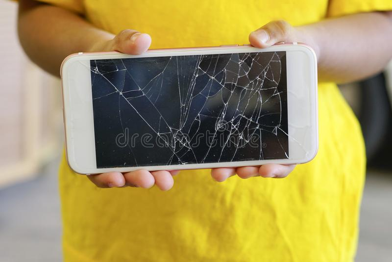 Kids holding a crack smartphone. Shallow DOF royalty free stock images