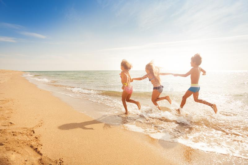 Kids holding hands and running along sandy beach royalty free stock photography