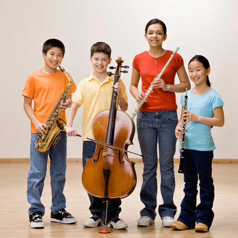 Kids holding saxophone, cello, flute and clarinet stock image