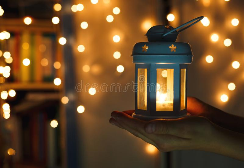 Kids holds Christmas lantern in hands on lights bokeh background. New year celebration concept stock image
