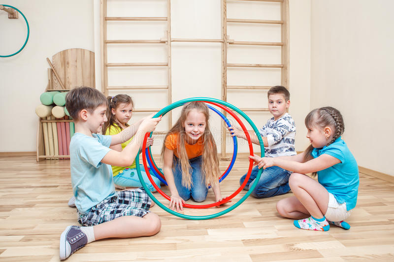 Kids with hula hoops. Cheerful kids playing with hula hoops in a school gym stock images