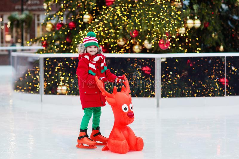 Kids ice skating in winter park rink. Children ice skate on Christmas fair. Little boy with skates on cold day. Snow outdoor fun royalty free stock photo