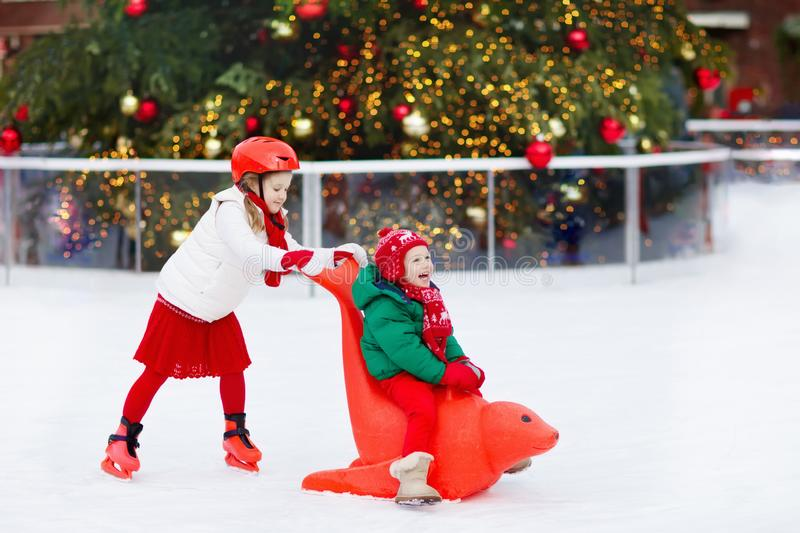 Kids ice skating in winter park rink. Children ice skate on Christmas fair. Little girl and boy with skates on cold day. Snow royalty free stock photos