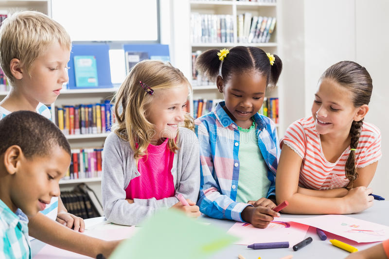 Kids interacting with each other in library stock photography