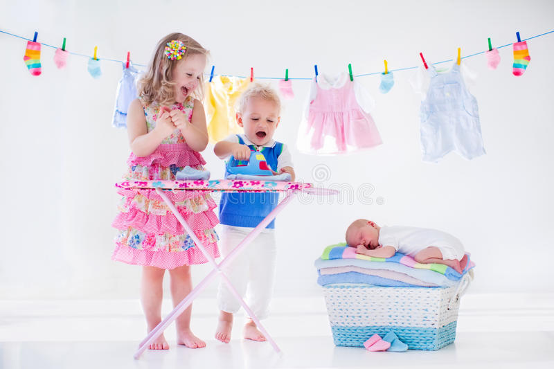 Kids ironing clothes for baby brother stock image