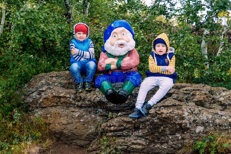 Kids and a jolly gnome royalty free stock photo