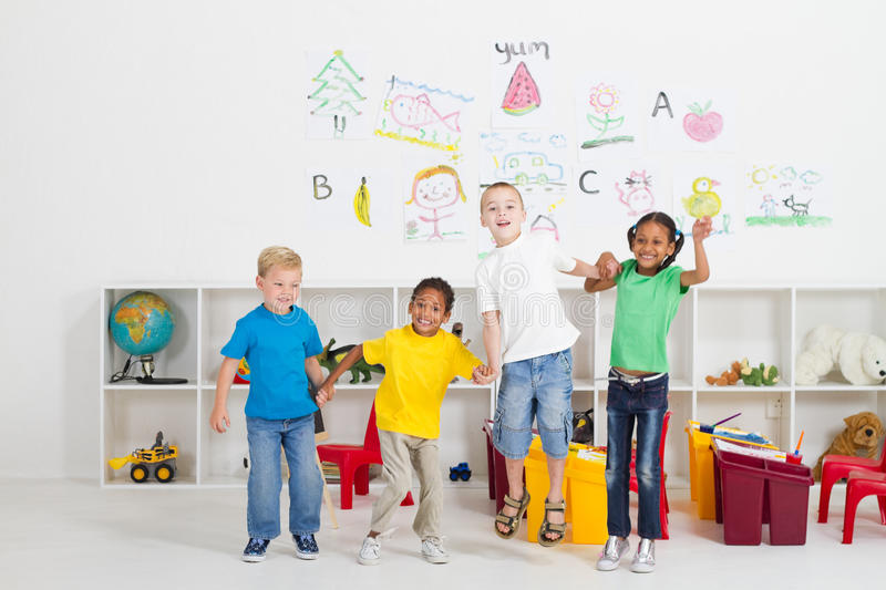Kids jumping. Four happy preschool kids jumping and holding hands in classroom stock photo