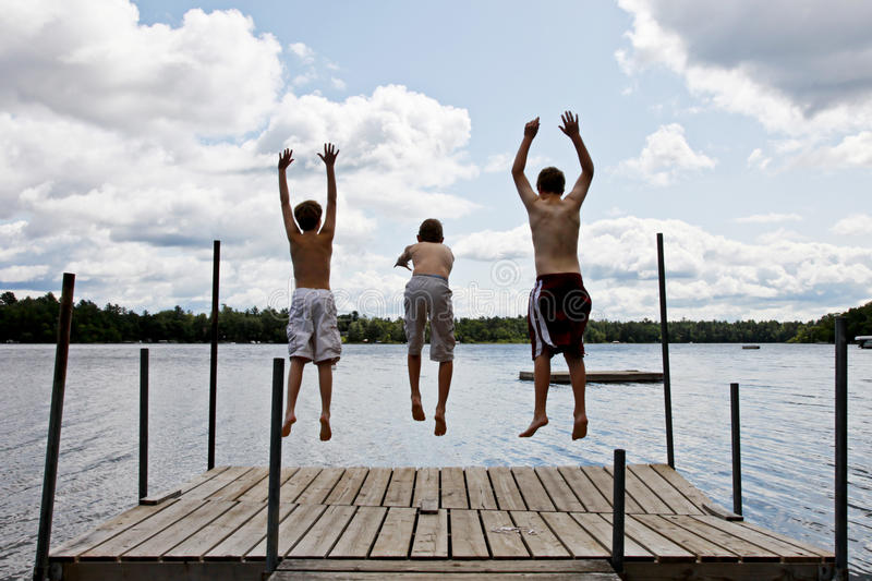 Kids jumping into Lake. A group of three boys jumping off on a dock into a lake at summer camp royalty free stock image