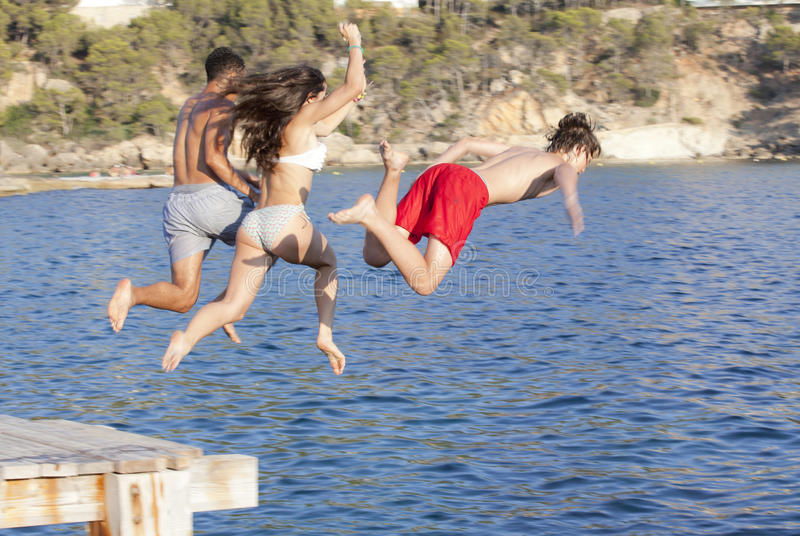 Kids jumping in ocean royalty free stock photo
