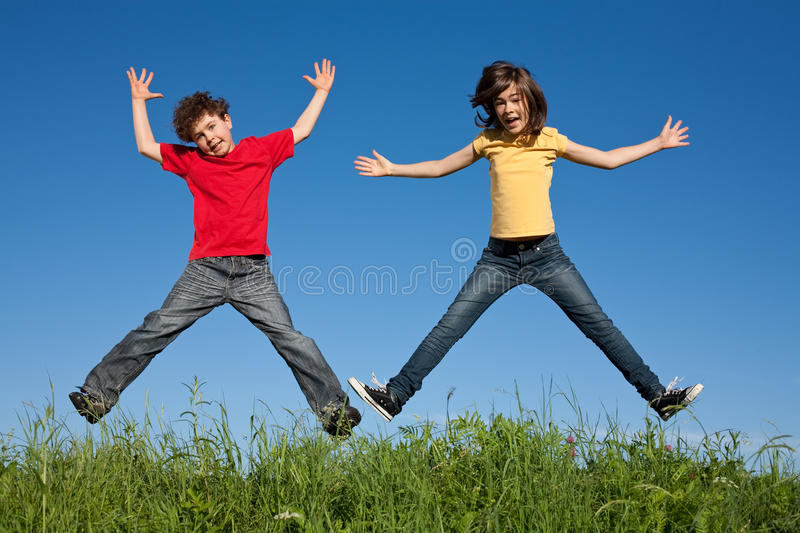 Kids jumping outdoor. Kids jumping against blue sky royalty free stock photography