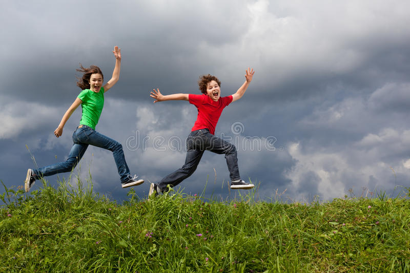 Kids jumping outdoor. Kids jumping against cloudy sky royalty free stock photography