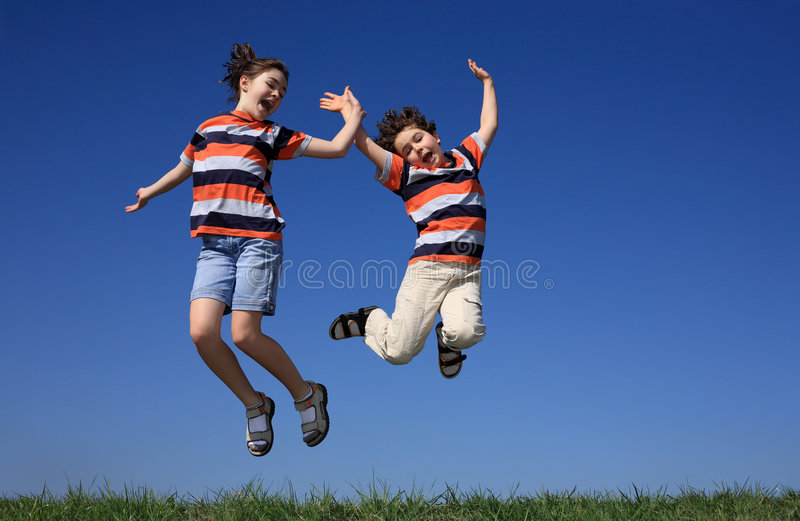 Kids jumping outdoor. Kids jumping against blue sky stock photo