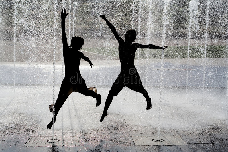 Kids jumping playing in fountain stock image