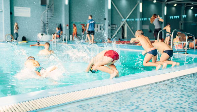 Kids jumping into pool with clean blue water stock images