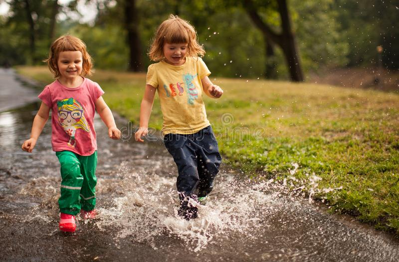 Kids Jumping into Water Puddle royalty free stock photo