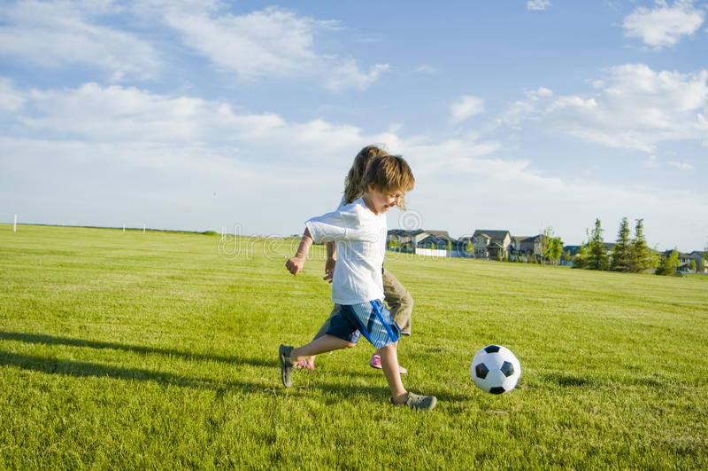 Kids Kicking Soccer Ball Royalty Free Stock Photography
