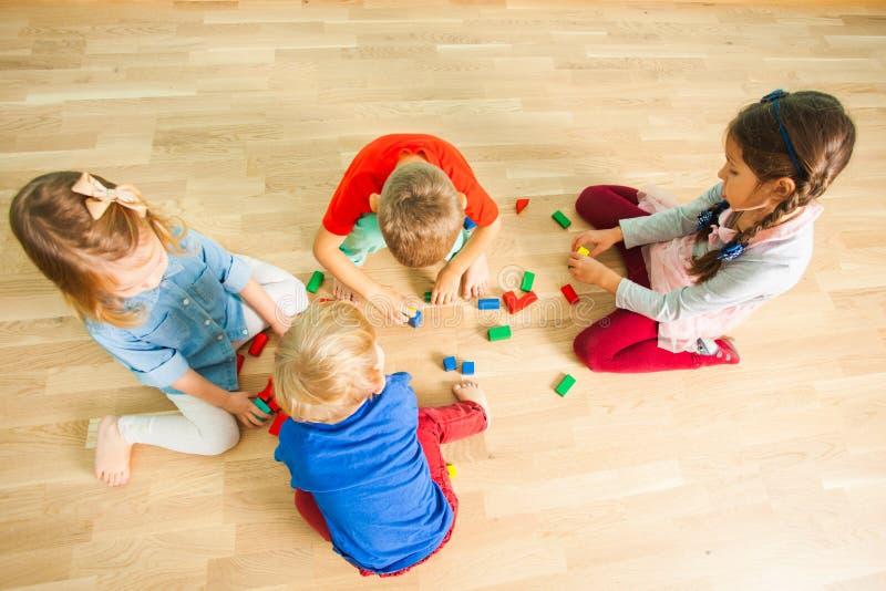 Kids in kindergarten building from wooden bricks stock images