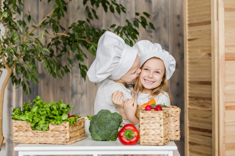 Kids in the kitchen making vegetable salads. Healthy food. Vegetables. Family. Kids in the kitchen making vegetable salads. Healthy food. Vegetables stock photography