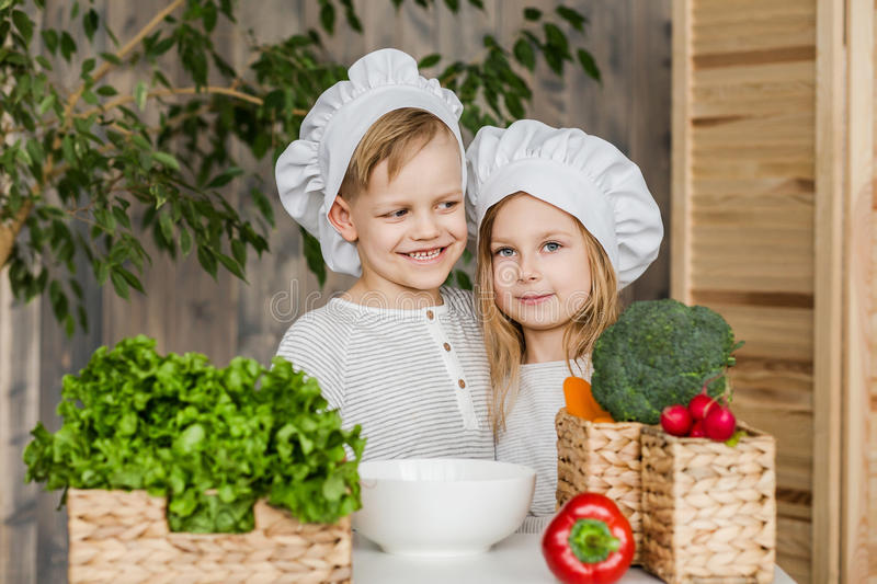 Kids in the kitchen making vegetable salads. Healthy food. Vegetables. Family royalty free stock photos