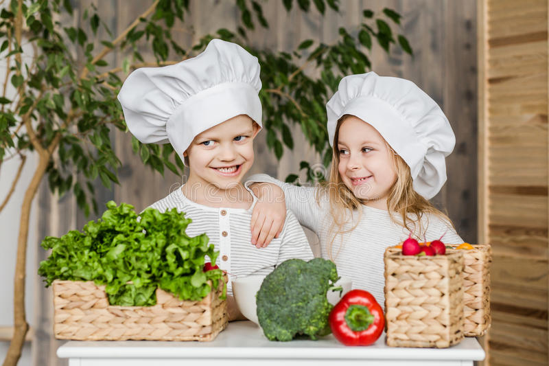 Kids in the kitchen making vegetable salads. Healthy food. Vegetables. Family. Handsome boy and beautiful young girl playing in the kitchen chefs. Healthy food royalty free stock photo