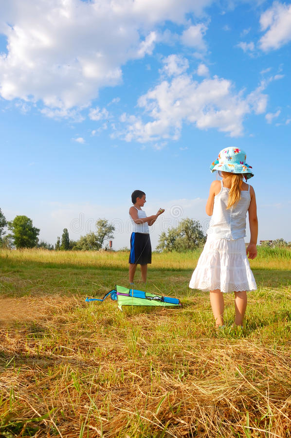 Kids with a kite. Two kids with a kite in the summer meadow stock image
