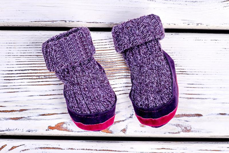 Kids knitted woolen room slippers. Childs warm purple winter socks on white wooden background. Childrens narural handmade garment stock images