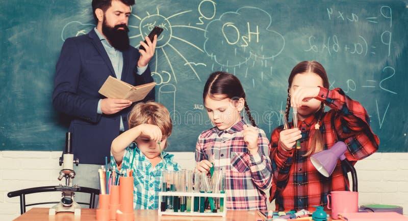 Kids in lab coat learning chemistry in school laboratory. chemistry lab. happy children teacher. back to school. making stock photo