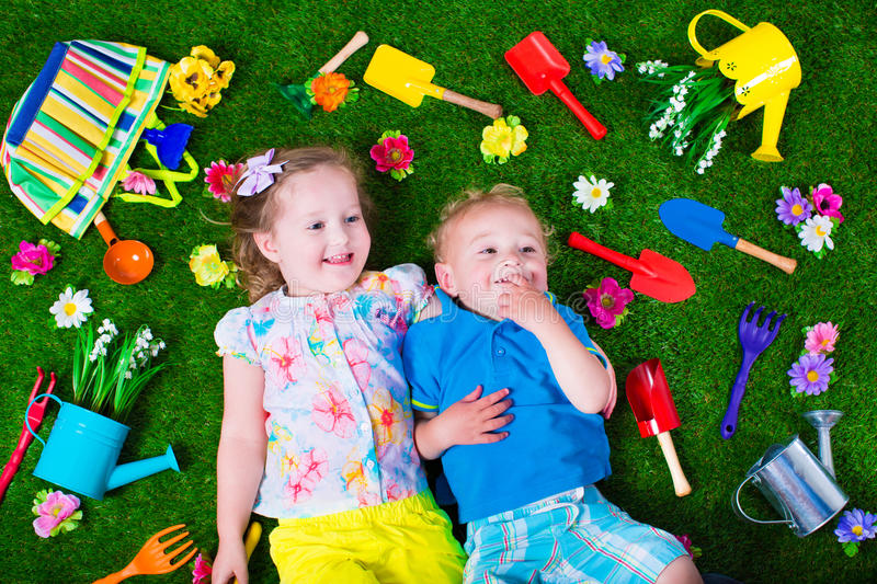 Kids on a lawn with garden tools. Kids gardening. Children with garden tools. Child with watering can and shovel. Little kid watering flowers. Girl and baby boy royalty free stock photography