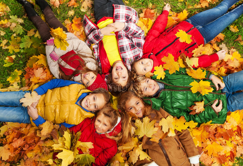 Kids lay on the autumn grass. Large group of kids laying in the grass with maple leaves all over them on autumn day stock photo