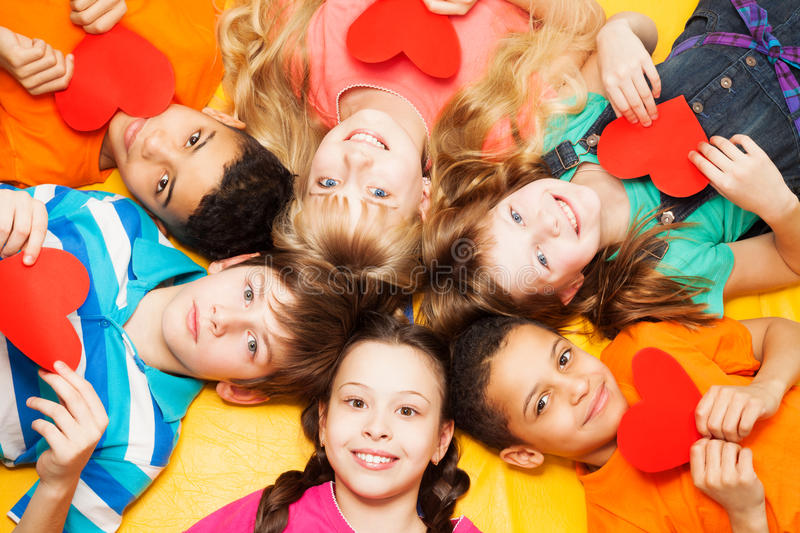 Kids laying in circle with hearts in their hands. Smiling, boys and girls with diversity royalty free stock image