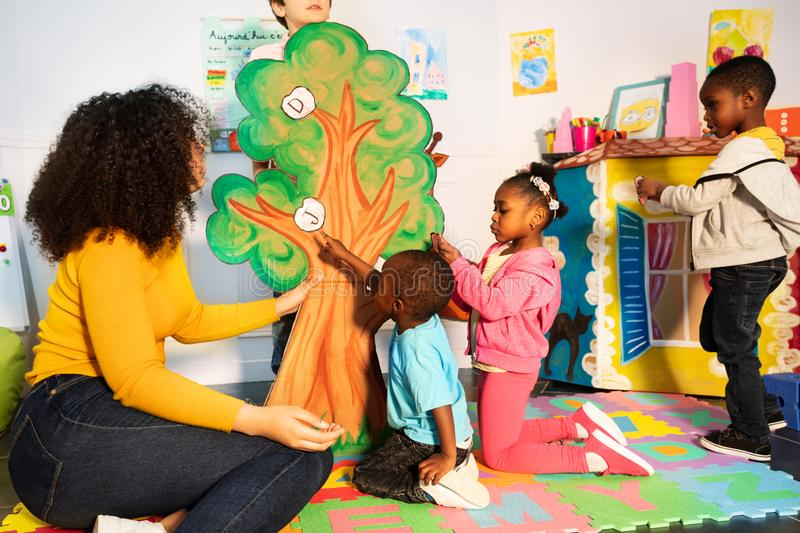 Kids learn alphabet put letters on tree in nursery. Group of black African descent looking kids learn alphabet by putting letters on the tree in kindergarten stock image