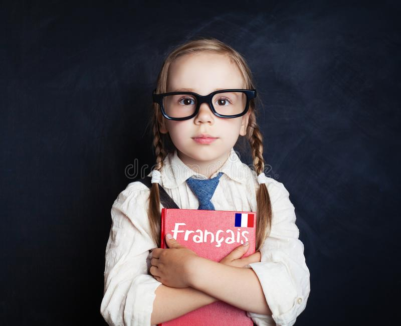 Kids learn French. Smart child girl with French book royalty free stock image